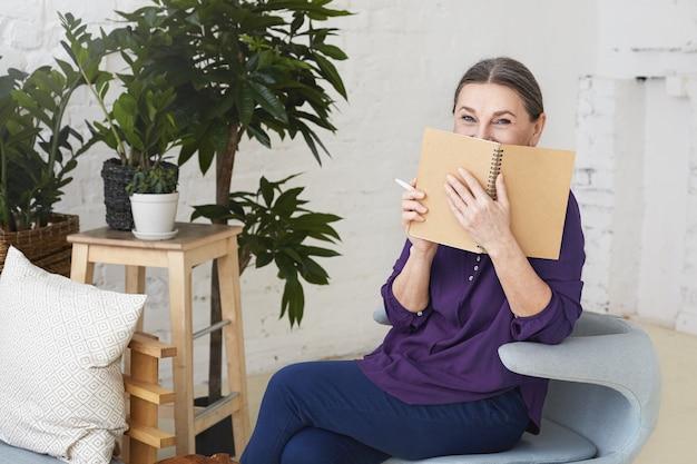 Atrakcyjna gospodyni domowa w średnim wieku na emeryturze siedząca na nowoczesnym fotelu w stylowym wnętrzu salonu, uśmiechnięta i zakrywająca twarz zeszytem podczas spisywania listy zakupów przed zakupami