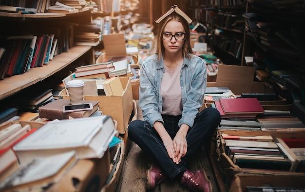 Atrakcyjna i miła dziewczyna stoi wśród dużych i długich regałów ze starymi książkami. trzyma w dłoni filiżankę kawy i patrzy na półkę. kobieta szuka książki