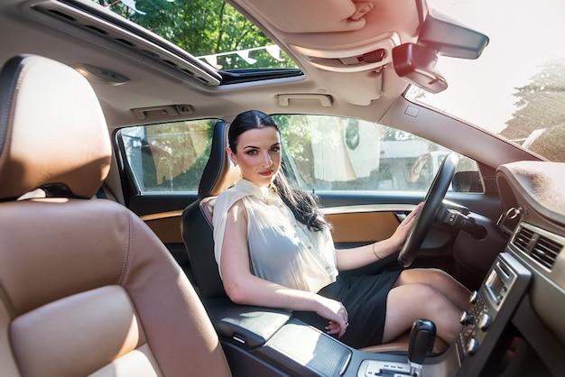 Atrakcyjna i piękna brunetka siedzi w samochodzie