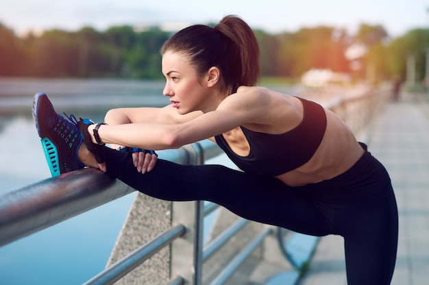 Atrakcyjna i silna kobieta rozciągająca się przed fitness na jeziorze w lecie. pojęcie sportu. zdrowy tryb życia