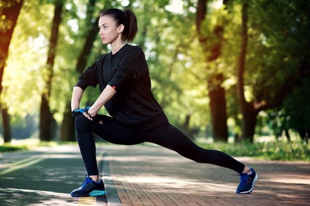 Atrakcyjna i silna kobieta rozciąganie przed fitness w parku lato. pojęcie sportu. zdrowy tryb życia