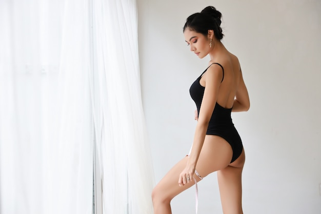 Atrakcyjna i sportowa szczupła kobieta mierząca talię za pomocą taśmy mierniczej