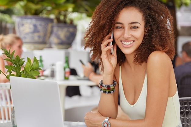 Atrakcyjna i zadowolona afroamerykanka pracuje zdalnie, siedzi w kawiarni na świeżym powietrzu, używa nowoczesnych gadżetów elektronicznych do komunikacji i surfowania po internecie.