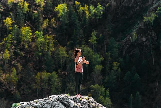 Atrakcyjna i zdrowa młoda kobieta ćwiczy jogę w górach o świcie. joga na świeżym powietrzu. szczęśliwa kobieta robi ćwiczenia jogi. medytacja w przyrodzie. kobieta ćwicząca jogę w górach
