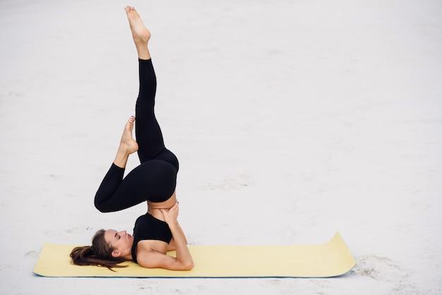 Atrakcyjna i zdrowa młoda kobieta robi ćwiczeniom na plaży o wschodzie lub zachodzie słońca. sprawności fizycznej dziewczyna robi rozciąganiu na joga macie. pojęcie zdrowego stylu życia.