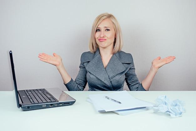 Atrakcyjna, inteligentna, wielozadaniowa blond kobieta (biznesowa dama) w stylowym garniturze pracuje z laptopem i kilkoma folderami zła i wściekła w panice w biurze. koncepcja biznesowa i termin realizacji