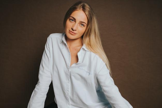 Atrakcyjna kaukaska blondynka w białej koszuli pozuje na brązowej ścianie