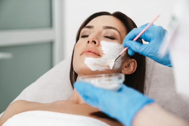 Atrakcyjna kaukaska kobieta poddawana zabiegowi kosmetycznemu przez specjalistę podczas leżenia w salonie kosmetycznym