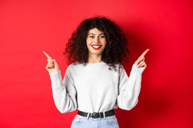 Atrakcyjna kaukaska kobieta pokazuje drogę, wskazuje palcem w bok na dwie promocje, demonstruje warianty i uśmiecha się, stojąc na czerwonej ścianie