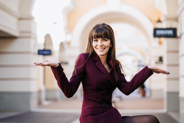 Atrakcyjna kaukaska kobieta ubrana w bordową sukienkę, rozkłada ręce po różnych stronach miasta. czas zakupów