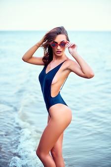 Atrakcyjna kaukaska kobieta w stroju kąpielowym bikini spaceruje po plaży o wschodzie słońca, ciesząc się dźwiękiem ...