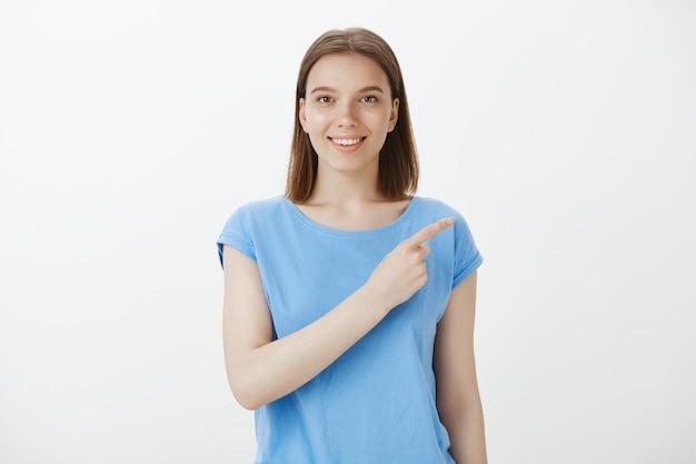 Atrakcyjna kaukaska kobieta wskazująca prawy górny róg i uśmiechnięta, zapraszająca do sprawdzenia oferty promocyjnej, specjalny baner rabatowy