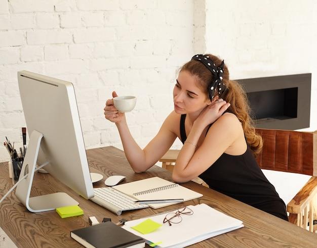 Atrakcyjna kaukaska studentka żartobliwie patrzy w monitor, rozmawia z przyjacielem przez wideokonferencję, pije kawę. ładna dziewczyna w chuście jest zainteresowana spojrzeniem na ekranie komputera