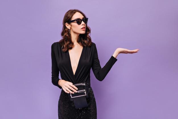 Atrakcyjna kędzierzawa dama w okularach przeciwsłonecznych i czarnej sukience wskazuje miejsce na tekst
