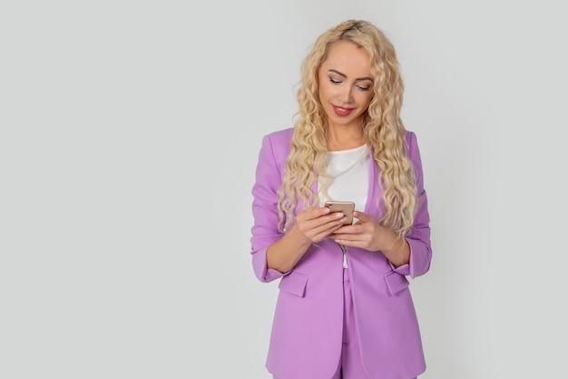 Atrakcyjna kobieca blondynka z długimi włosami, uśmiechnięta i śmiejąca się, ogląda wideo, ogląda smartfon