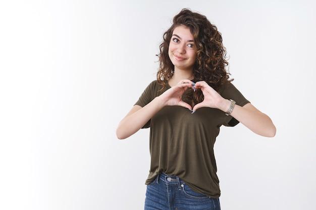 Atrakcyjna kobieca delikatna młoda kaukaska kobieta z kręconymi włosami na sobie t-shirt pokaż kształt serca w pobliżu klatki piersiowej uśmiechając się szczęśliwie wyrażaj sympatię miłość przyjaźń pielęgnować pasję, białe tło