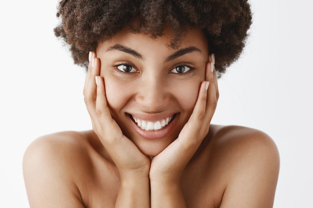 Atrakcyjna, kobieca i naturalna młoda afroamerykanka o kręconych włosach i czystej, czystej skórze, dotykająca twarzy i szeroko uśmiechnięta z podniecenia i szczęścia, pozująca nago nad szarą ścianą