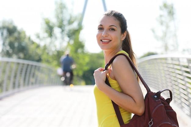 Atrakcyjna kobieta backpacker spacery po moście w parku przyrody, patrząc na kamery. skopiuj miejsce.