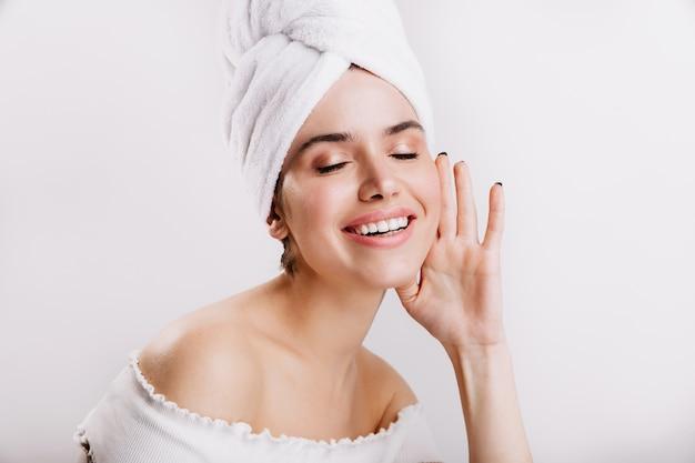 Atrakcyjna kobieta bez makijażu, pozowanie na białej ścianie. ujęcie brunetki w ręcznik na głowie.