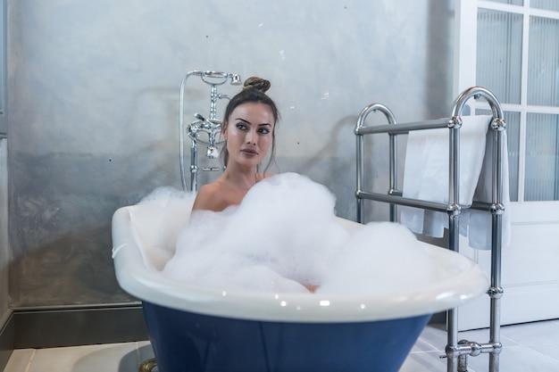 Atrakcyjna kobieta biorąc pienista kąpiel