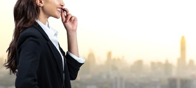 Atrakcyjna kobieta biznesu i zestawy słuchawkowe uśmiechają się podczas pracy. asystent obsługi klienta pracuje
