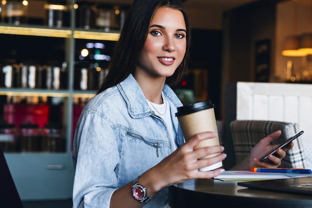 Atrakcyjna kobieta biznesu siedzi przy stole przed laptopem i rozmawia przez telefon komórkowy, negocjuje przez telefon.