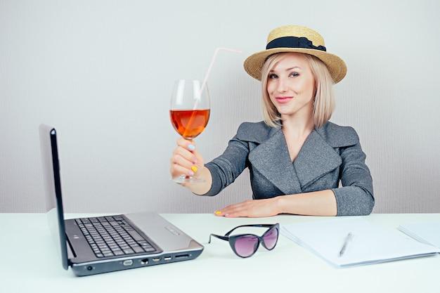 Atrakcyjna kobieta blondynka (biznes pani) w stylowym garniturze i słomkowym kapeluszu marzy o wakacjach w biurze z koktajlem i laptopem na stole. koncepcja podróży i wakacje