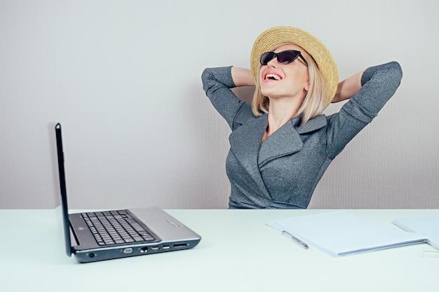 Atrakcyjna kobieta blondynka (biznesowa dama) w stylowym garniturze, w okularach przeciwsłonecznych i słomkowym kapeluszu marzy o wakacjach i opalaniu się w biurze z laptopem na stole. koncepcja podróży i wakacje