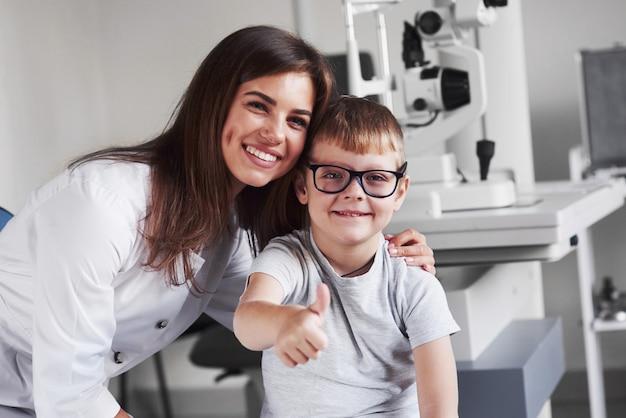 Atrakcyjna kobieta blondynka młody lekarz uśmiechając się z jej zadowolonym małym pacjentem. okulary są idealnie dobrane.