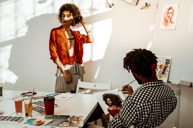 Atrakcyjna kobieta. chuda atrakcyjna kobieta ubrana w czerwoną bluzkę stojąca w pobliżu białej ściany pozuje do portretu