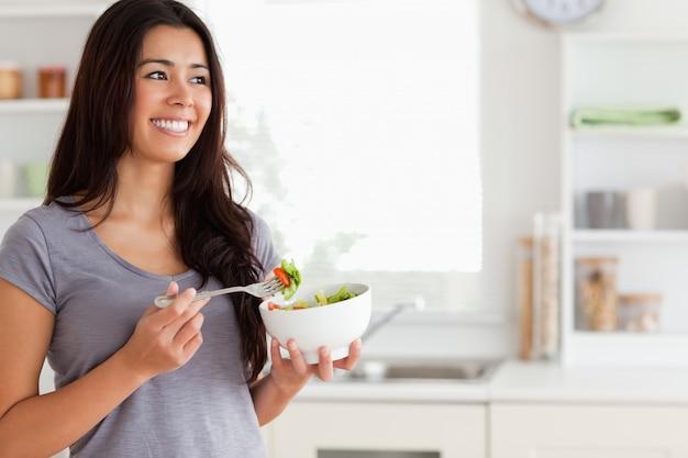 Atrakcyjna kobieta cieszy się puchar sałatka podczas gdy stojący