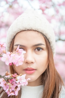 Atrakcyjna kobieta cieszy się z cherry blossom w parku