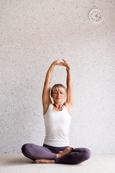 Atrakcyjna kobieta ćwicząca jogę w domu, ubrana w białą koszulę sportową i fioletowe spodnie
