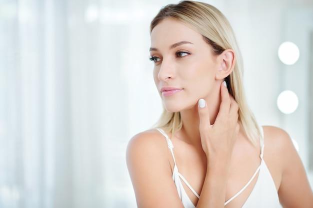 Atrakcyjna kobieta dotyka nieskazitelnej skóry