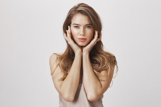 Atrakcyjna kobieta dotyka twarzy i patrząc zmysłowy aparat