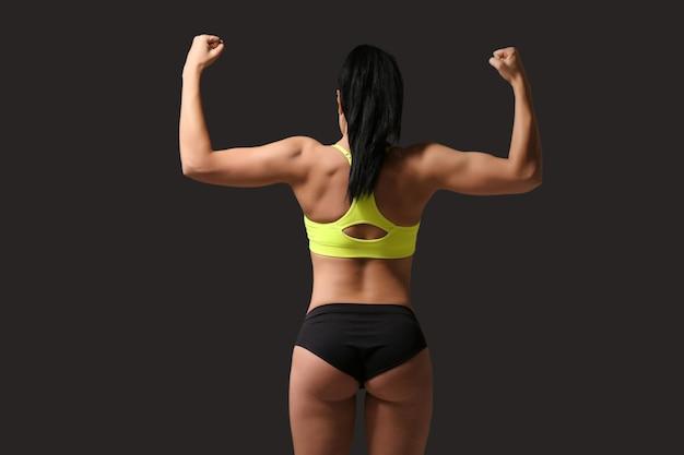 Atrakcyjna kobieta fitness na ciemnoszarym