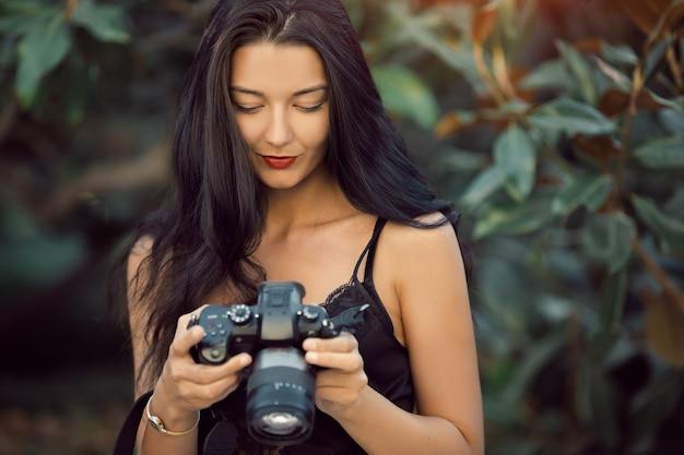 Atrakcyjna kobieta fotograf robienia zdjęć aparatem dslr na zewnątrz w parku. cudownie szczęśliwy