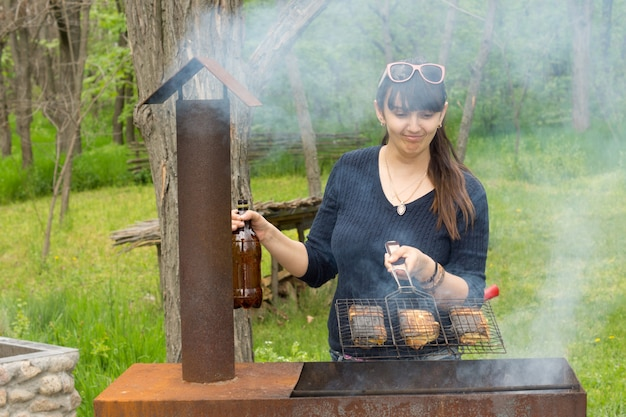 Atrakcyjna kobieta gotuje na piknikowym grillu
