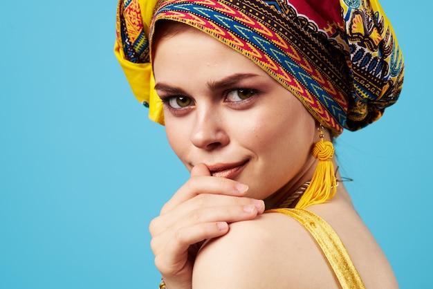 Atrakcyjna kobieta jasny makijaż dekoracji pochodzenie etniczne wielobarwny turban niebieska ściana.