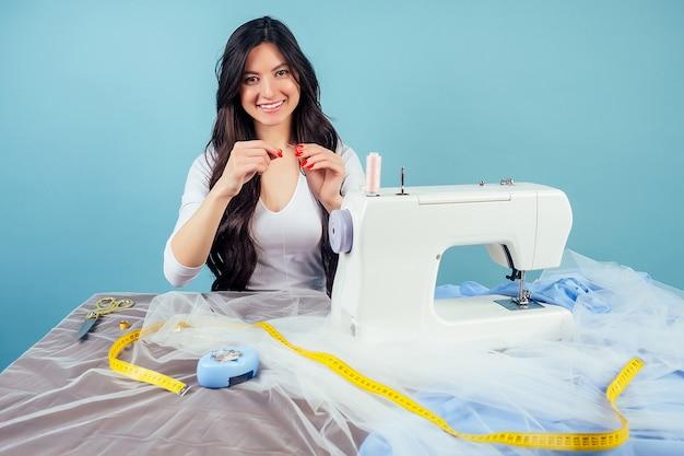 Atrakcyjna kobieta krawcowa ślubna krawcowa (szwaczka) wątek igły na maszynie do szycia na niebieskim tle w studio. koncepcja stworzenia nowej kolekcji sukni ślubnej