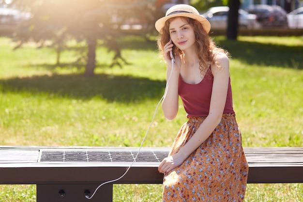 Atrakcyjna kobieta ładująca swój telefon za pomocą bezpłatnego wielofunkcyjnego panelu słonecznego wbudowanego w ławkę dla obywateli