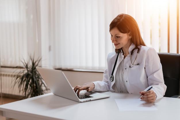 Atrakcyjna kobieta lekarz pracuje na swoim laptopie w swoim biurze