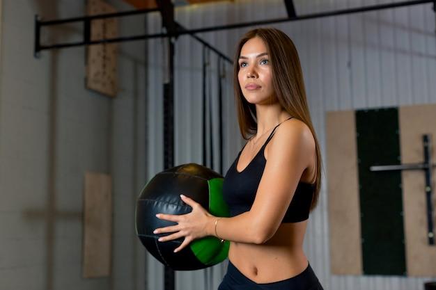 Atrakcyjna kobieta lekkoatletka stoi na siłowni trzymając piłkę