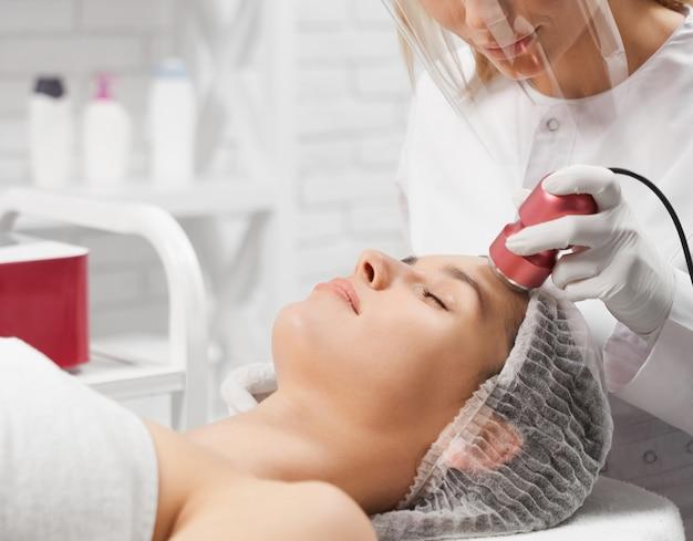 Atrakcyjna kobieta leży na twarzy procedury czyszczenia