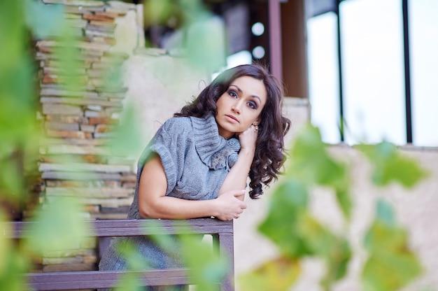 Atrakcyjna kobieta moda w szarej sukience pozowanie w pobliżu domu.