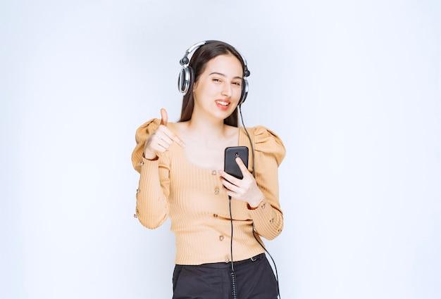 Atrakcyjna kobieta model słucha muzyki w słuchawkach i wskazuje na telefon komórkowy.