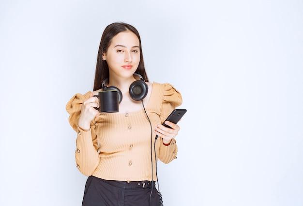 Atrakcyjna kobieta model trzyma kubek z telefonem komórkowym i słuchawkami.