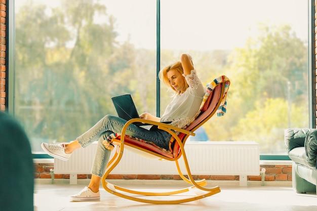 Atrakcyjna kobieta na bujanym fotelu z notesem w rękach i bardzo przemyślanym spojrzeniem. zdjęcie wnętrza, pusta przestrzeń.