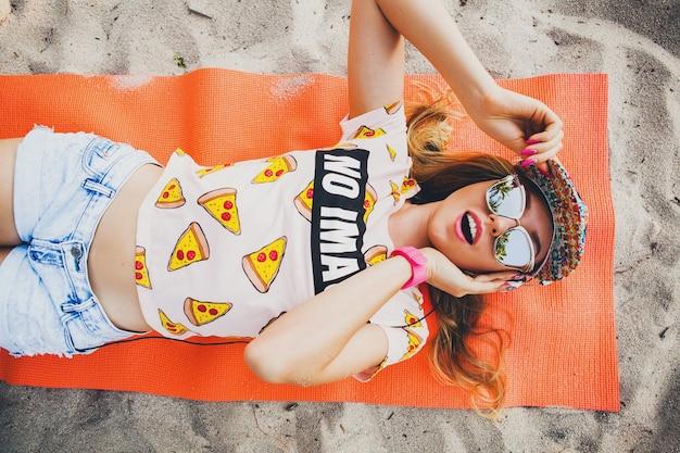 Atrakcyjna kobieta na plaży słuchająca muzyki na słuchawkach w stylowym, kolorowym stroju na letnich tropikalnych wakacjach w okularach przeciwsłonecznych z akcesoriami, uśmiechnięta szczęśliwa leżąca na macie do jogi widok z góry