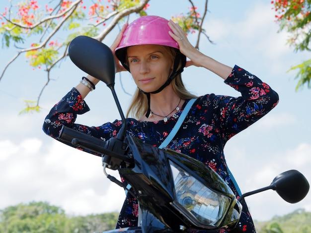 Atrakcyjna kobieta na skuterze napina różowy kask.